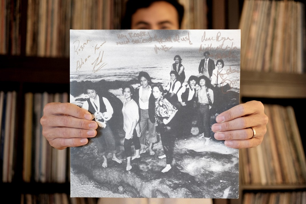 Roger Bong holds his copy of the compilation, featuring autographs from the artists.